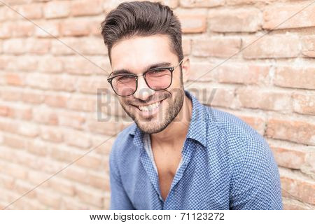 closeup picture of a happy smiling young casual man with glasses leaning against brick wall