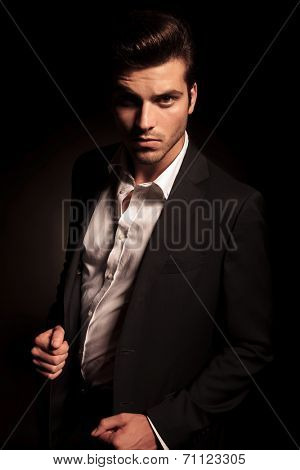 cool fashion man in suit pulling his coat in a fashion pose, in studio