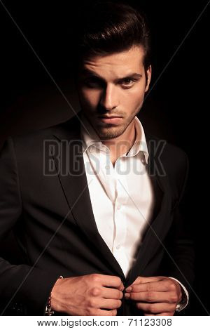 portrait of a young fashion man buttoning his suit on black studio background