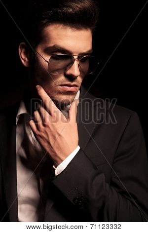 dramatic pensive young man in suit and sunglasses looking thoughtful on black background