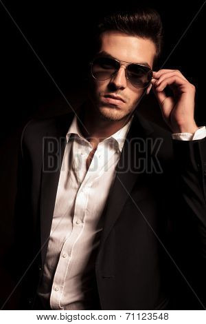 portrait of a sexy young fashion man putting on his sunglasses on black background