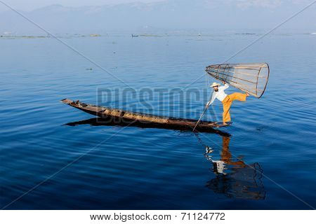 Myanmar travel attraction landmark - Traditional Burmese fisherman balancing with fishing net  at Inle lake, Myanmar famous for their distinctive one legged rowing style