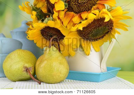 Beautiful sunflowers in pitcher with cups and pears on table on bright background