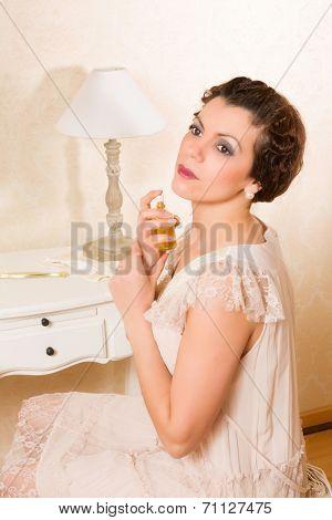 Beautiful vintage 1920s woman applying perfume in her boudoir