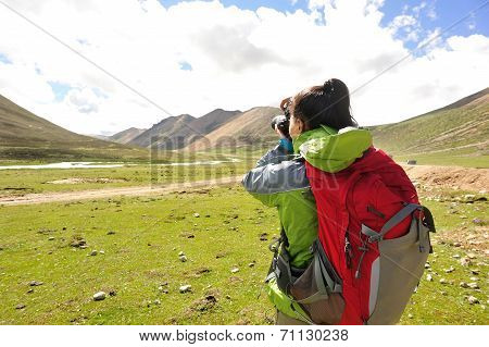 woman photographer taking photo at plateau mountain peak in tibet,china