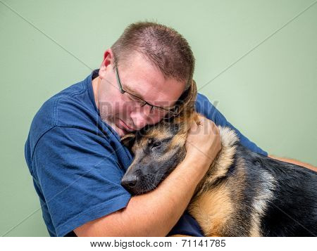 Young man hugging and consolating his dog