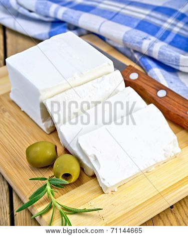 Feta With Olives And Rosemary On Board With Knife