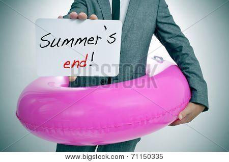 businessman with a pink swim ring showing a signboard with the text summers end written in it