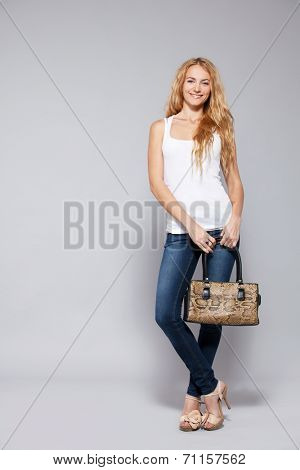 Happy woman with handbag in studio