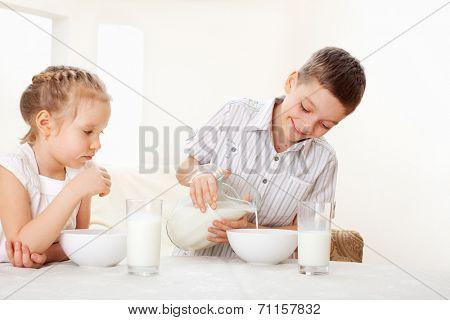 Children eat breakfast. Family eating cereals with milk