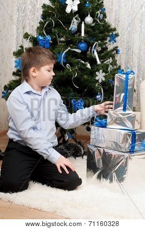 Boy With Gifts Near A Christmas Tree