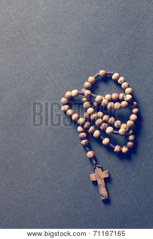 wooden rosary beads on black background