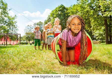 African girl play crawling through tube in park
