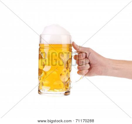 Mug of beer with foam in hand.