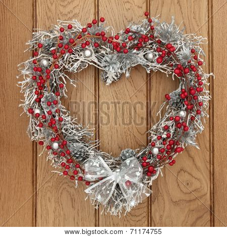 Heart shaped christmas yule wreath with red and silver bauble decorations over oak background.