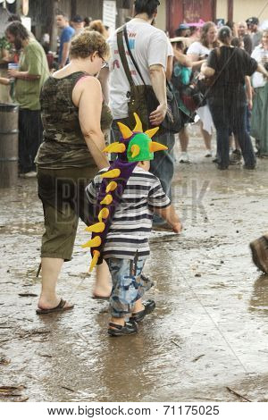 MUSKOGEE, OK - MAY 24: Kid dressed as a dragon walks in mud and water and mud after rain at the Oklahoma 19th annual Renaissance Festival on May 24, 2014 at the Castle of Muskogee in Muskogee, OK.