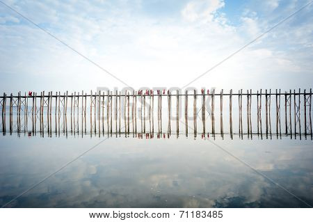 U bein bridge in Myanmar with many Buddhist monks crossing it at early morning sunrise