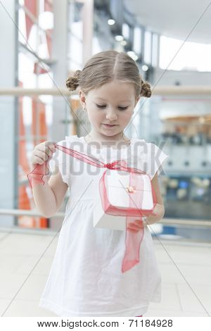 Young girl unwrapping ribbon on present