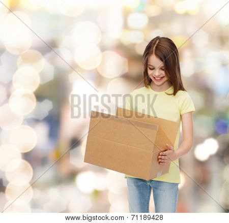 advertising, childhood, delivery, mail and people - smiling girl holding open cardboard box and looking into it over holidays background