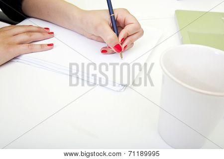 Close up of womans hands writing on paper.