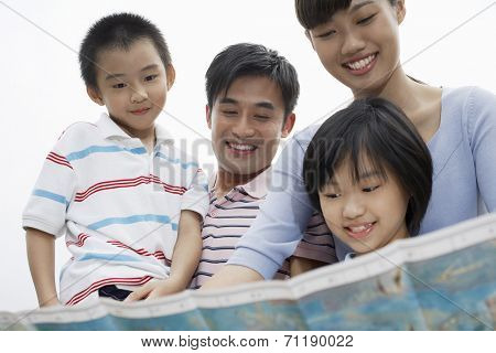 Family including boy and girl (7-9) reading map outdoors