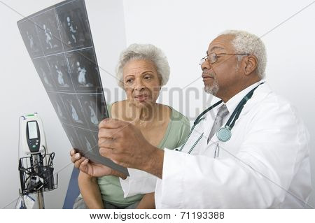 Senior practitioner  and patient examine xray
