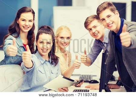 education, techology and internet concept - group of smiling students with computer monitor and tablet pc