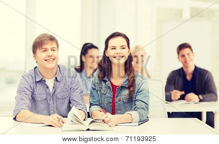 education, school and people concept - two teenagers with notebooks amd book listening to someone at school