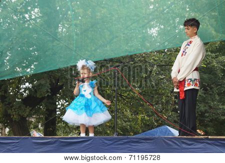 Mstyora,Russia-August 16,2014: Small woman reads poem on scene at day of the city