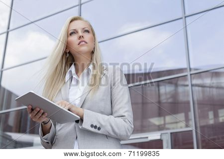 Low angle view of businesswoman holding digital tablet while looking away against office building
