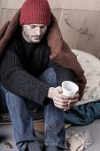stock photo of homeless  - Cold and sad homeless man begs for money - JPG
