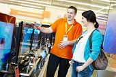 stock photo of tv sets  - Young woman choosing tv set with shop assistant in home appliance shopping mall supermarket - JPG