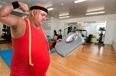 stock photo of obese man  - Large unhappy fitness man with weight scale in a gym - JPG
