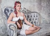foto of gothic hair  - Beautiful steampunk woman with pink hair and trousers on the sofa - JPG