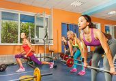 foto of lifting weight  - Group of girls exercising in the fitness club lifting dumbell with weights - JPG