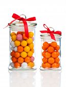 foto of gumballs  - Colorful background of assorted Gumballs in glass jar isolated over white background - JPG