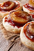 image of patty-cake  - Cakes of puff pastry with plums macro on an old table - JPG