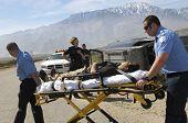 stock photo of stretcher  - Paramedics transporting victim on stretcher - JPG