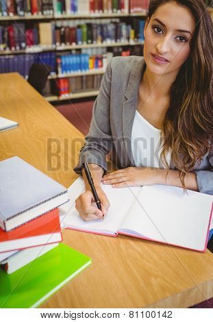 Smiling brunette student doing her assignment in librar