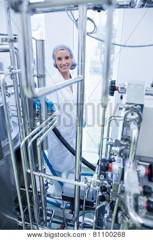 Smiling scientist behind metal pipe in the factory