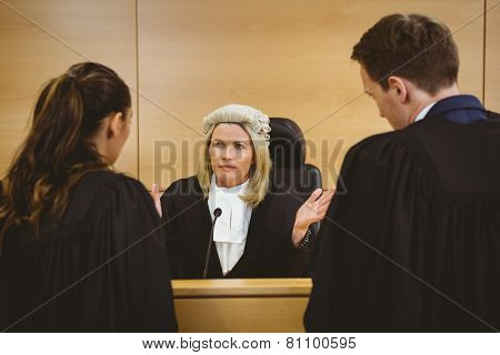 Judge wearing a dress and a wig speaking with lawyers in the court room