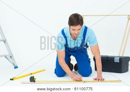 Handsome worker marking on wood while measuring over white background