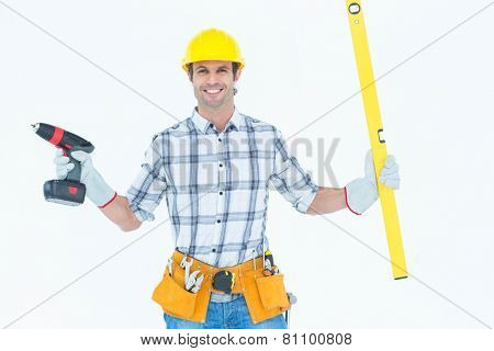 Portrait of confident technician holding portable drill and spirit level over white background