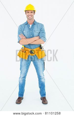 Portrait of confident carpenter standing arms crossed over white background