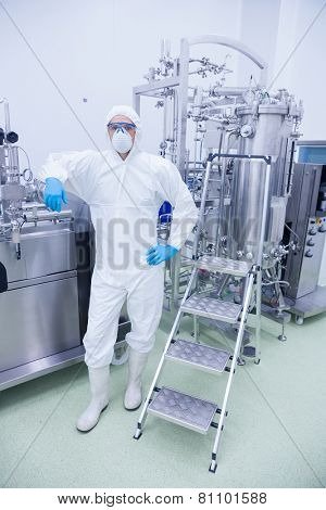 Scientist in protective suit leaning against machine in the factory