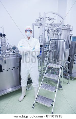 Scientist in protective suit standing with arms crossed in the factory