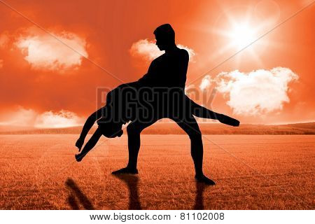 Ballerina leaping against sunny brown landscape