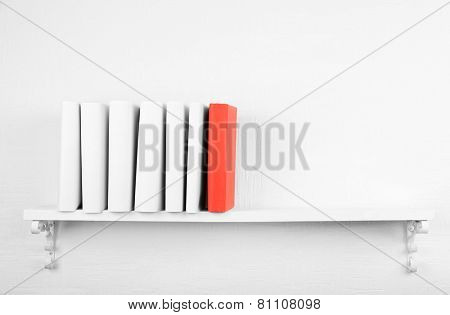 Blank books with red one on bookshelf on white wall background