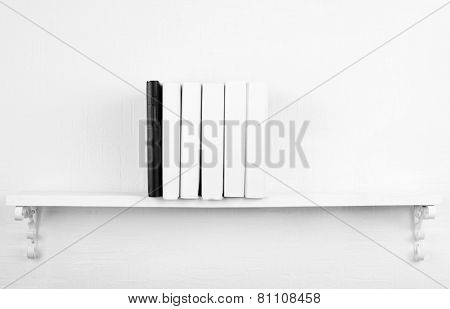 Blank books with black one on bookshelf on white wall background
