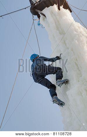 Man climbs upward on ice climbing competition